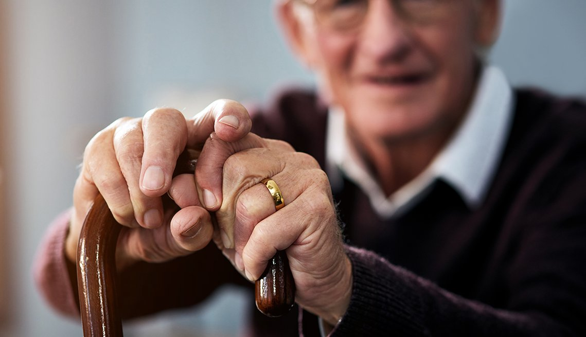 Un adulto mayor sosteniendo un bastón.
