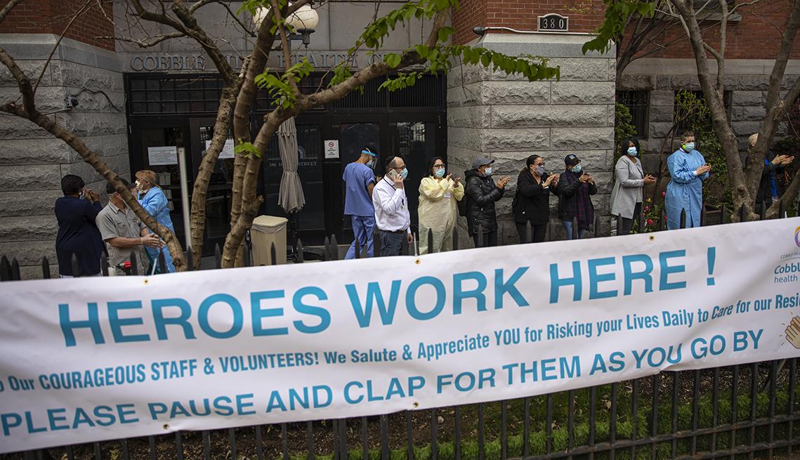 Trabajadores usando equipo de protección afuera de un hogar de ancianos  con un cartel que dice los héroes trabajan aquí