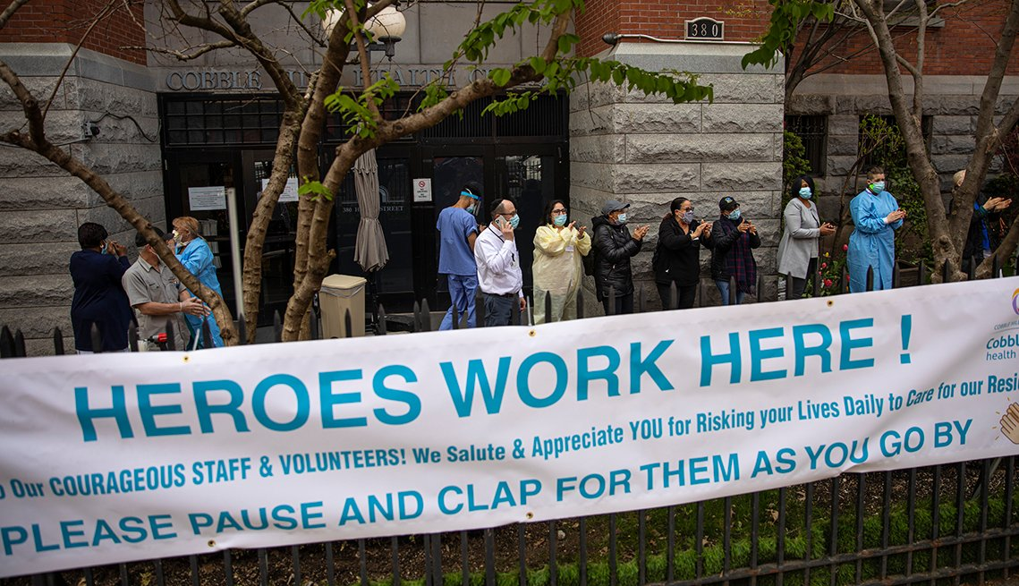 Workers wearing protective gear outside a nursing home with a sign that says heroes work here