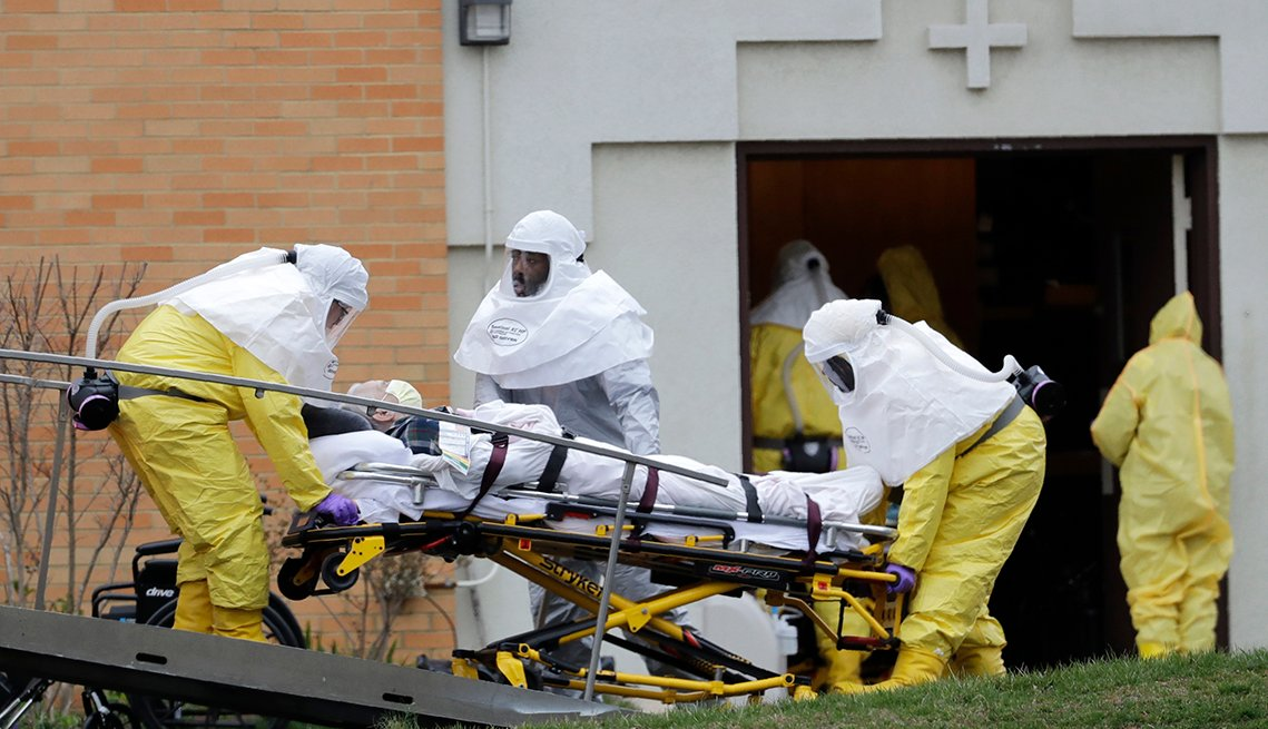 A man on a stretcher being moved from a nursing home by three people wearing medical protective gear
