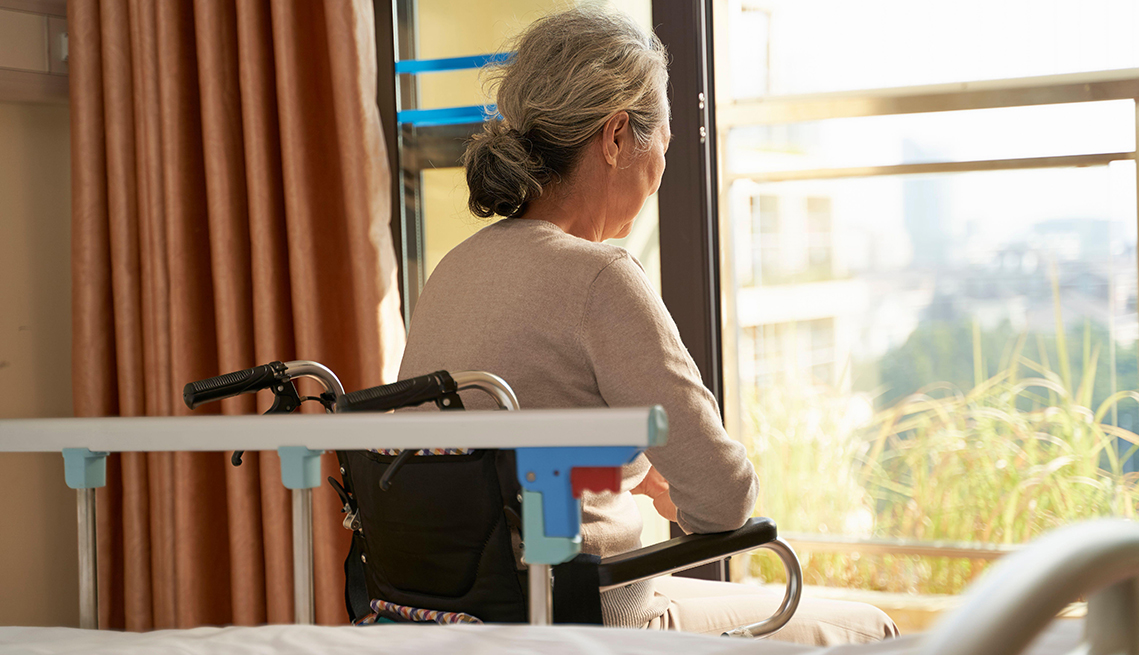 Rear view of a woman in a nursing home room sitting in wheel chair looking out the window