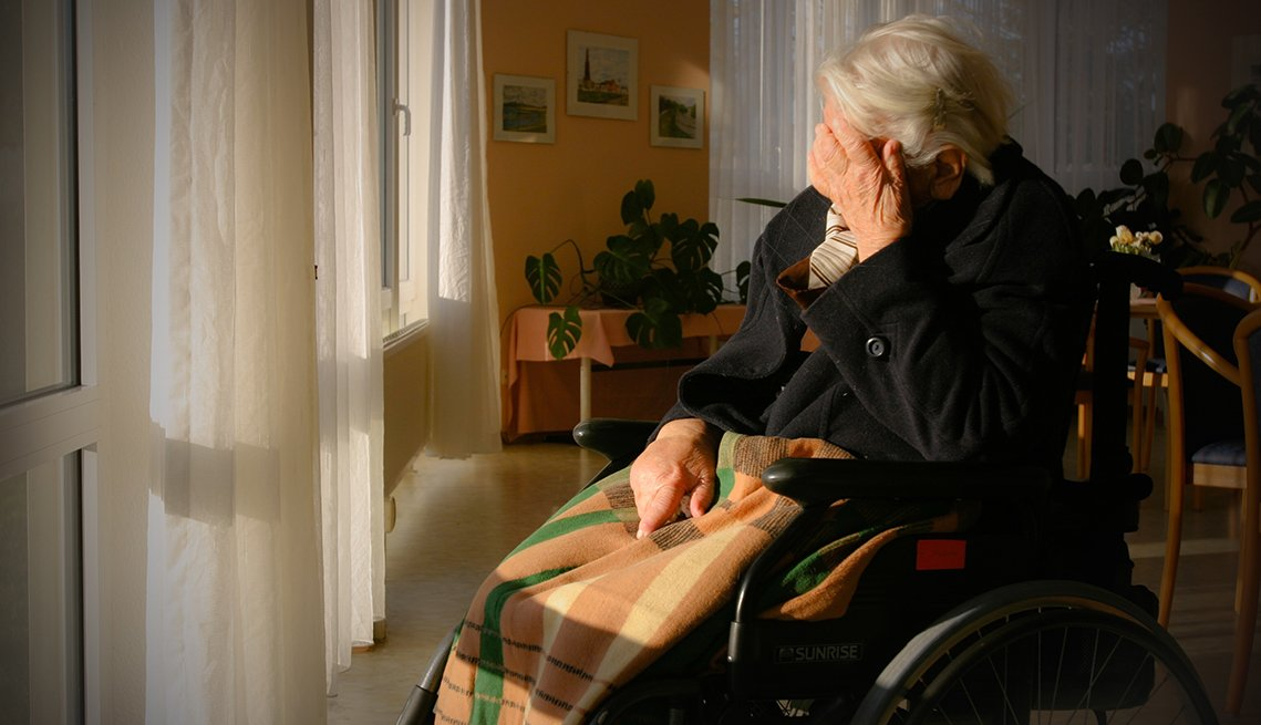 A man sitting in a wheelchair in a nursing home with his head in his hand, looking sad