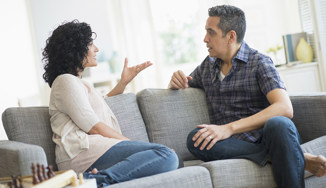 Adult brother and sister sitting on the couch having an argument