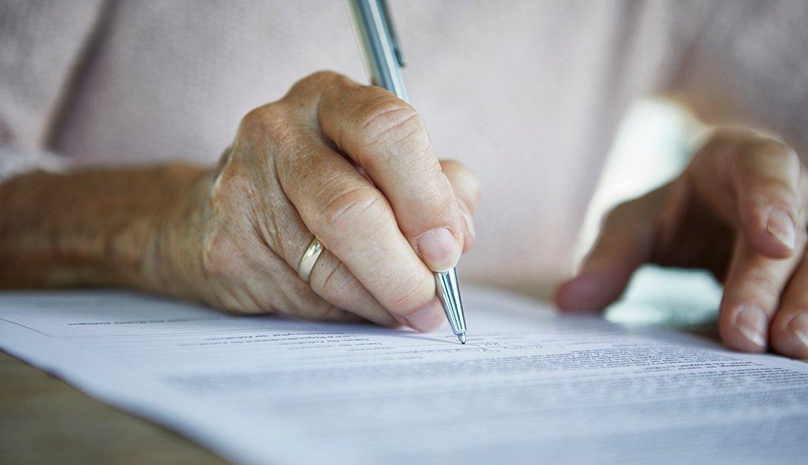 Una mujer firma un documento