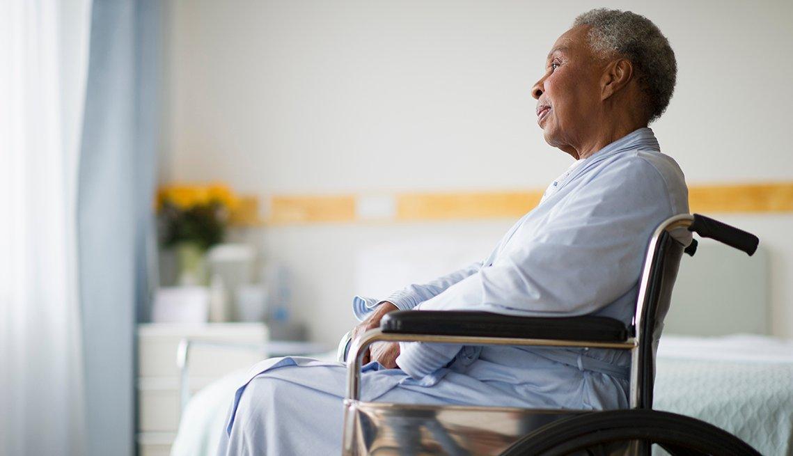 Mujer en sillas de ruedas mira por la ventana en un hogar de ancianos