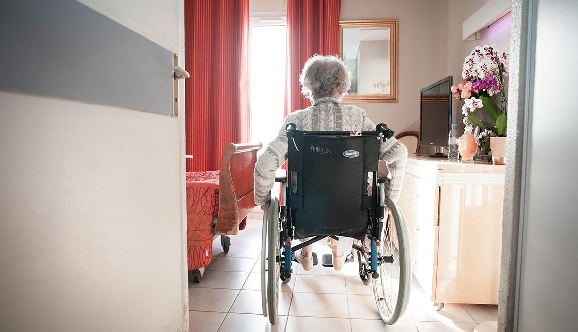 A woman sitting in a wheelchair in her nursing home room