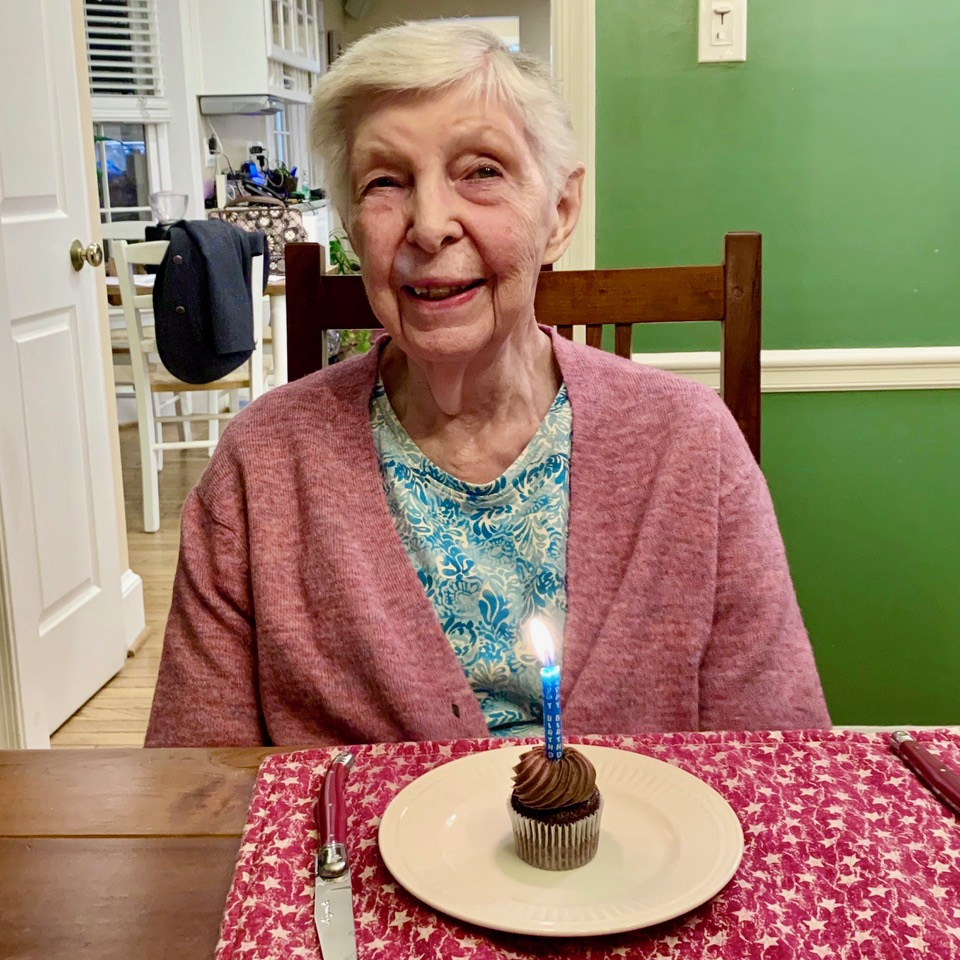 Margaret Kaplan sitting in front of a cupcake with a birthday candle in it