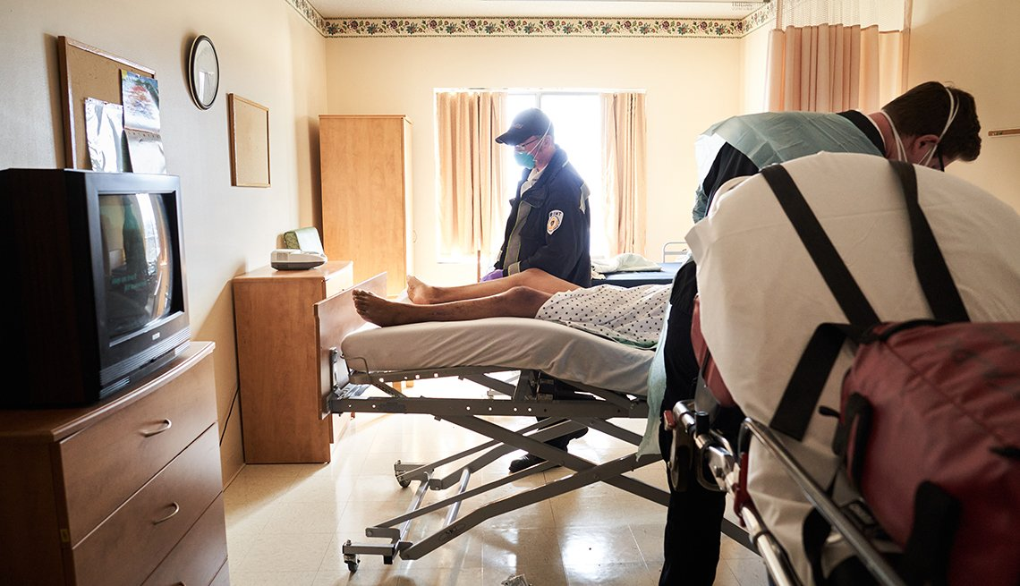 two E M S workers picks up a suspected Covid 19 patient at a nursing home
