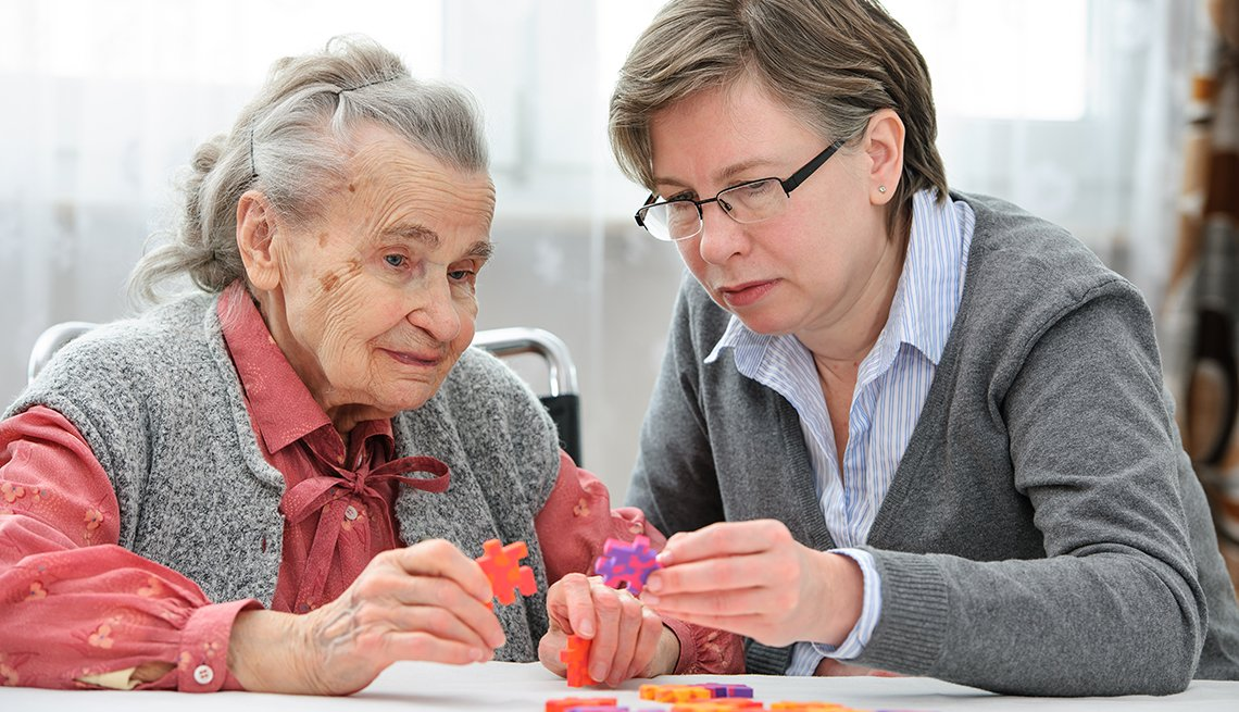Woman doing a puzzle with her mother who has Alzheimer's