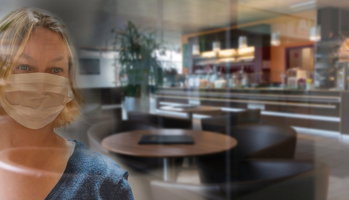 Una mujer usando una mascarilla mira un restaurante vacío a través de un cristal