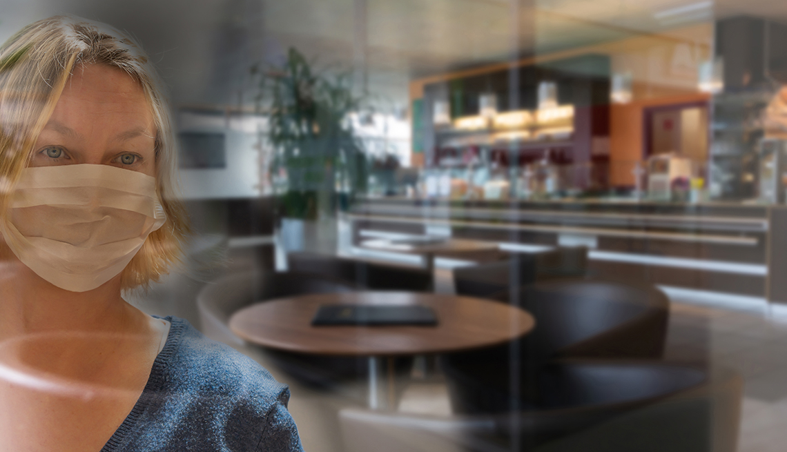 woman wearing a face mask looking through the window of a restaurant