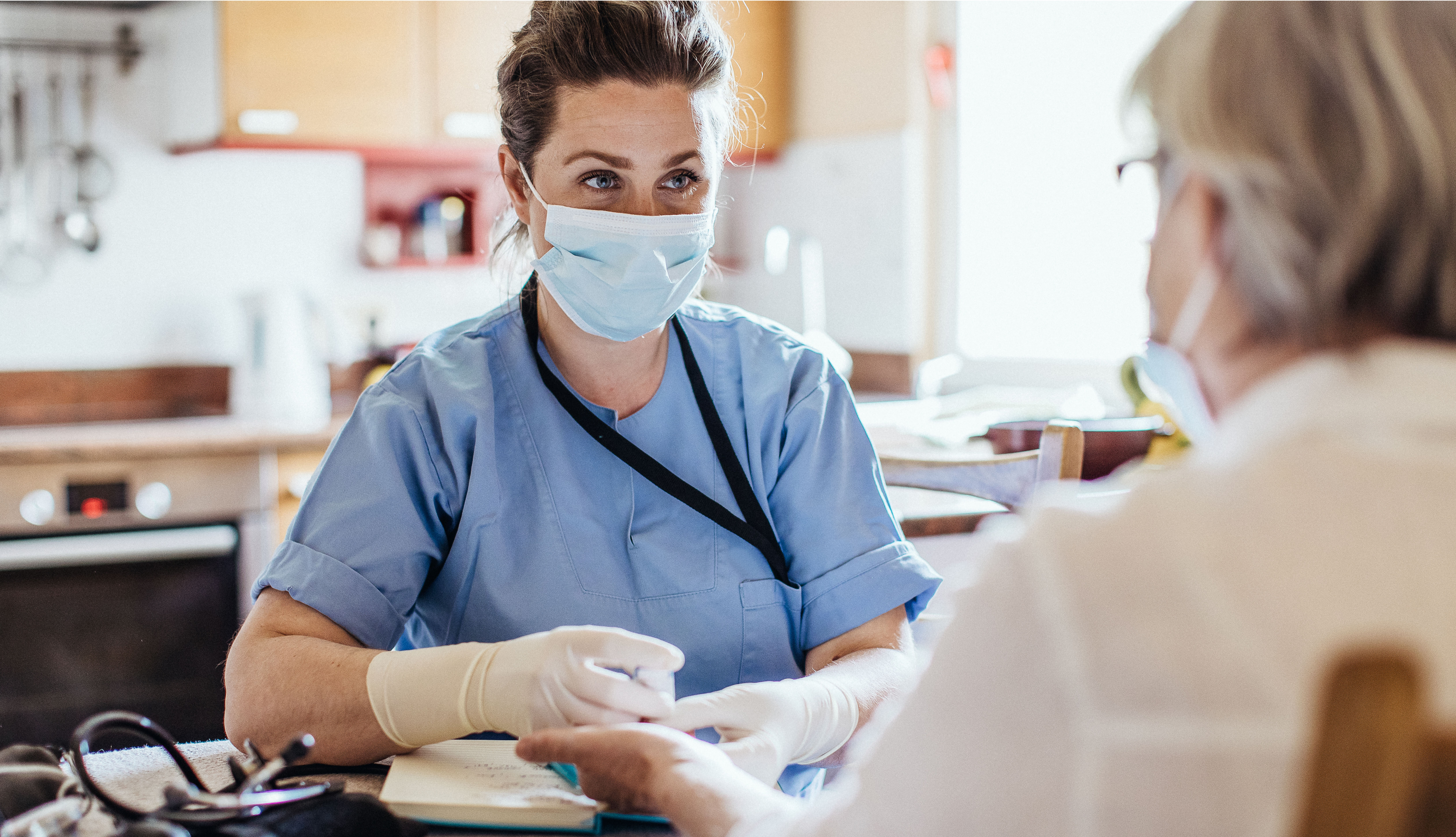 hospice worker wearing mask and gloves taking care of older patient wearing gloves