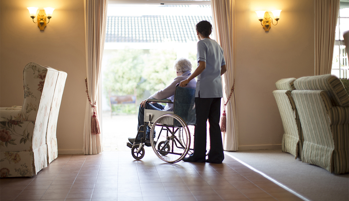 Nurse pushing patient in wheelchair at assisted living facility