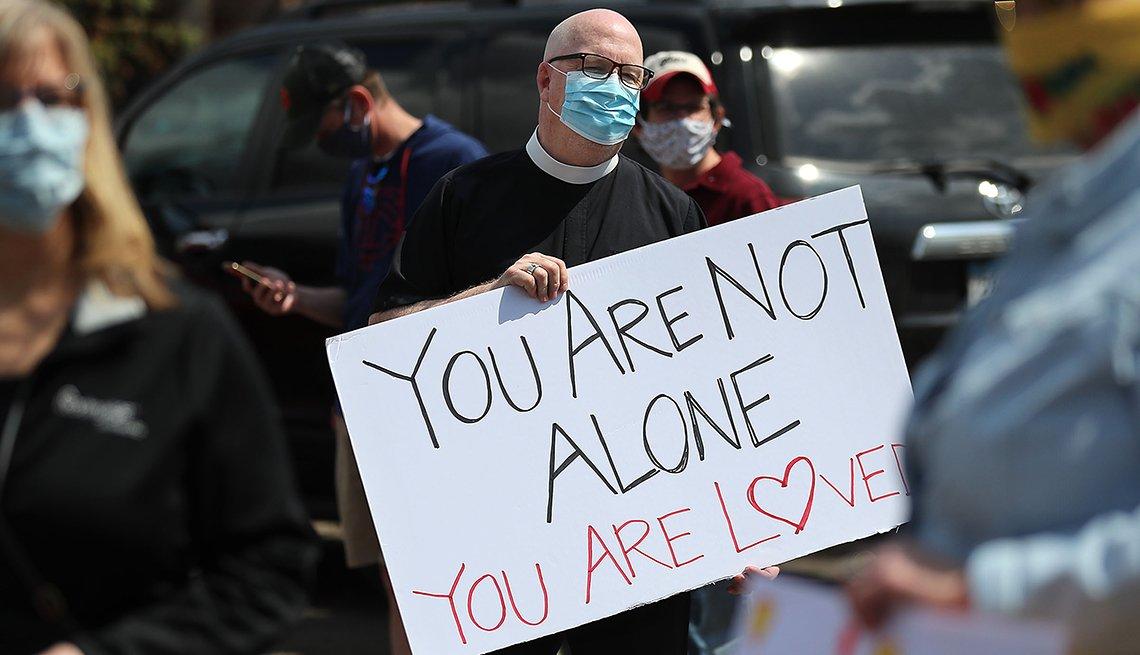 Un hombre sostiene un cartel que dice no estás solo, alguien te ama