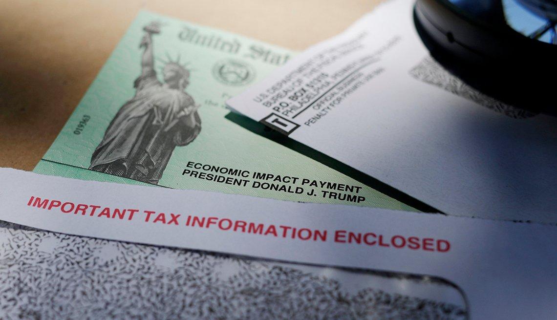 Cheque de estímulo  y otros documentos sobre impuestos sobre una mesa