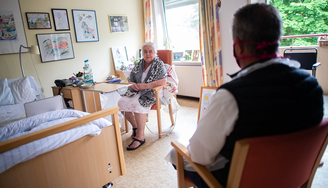 Man visiting his mother in her nursing home sitting in the chair across the room from her and wearing a face mask