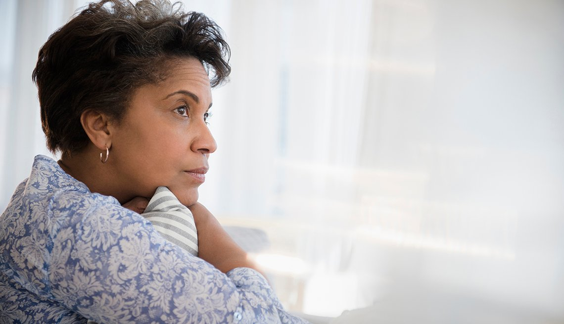 Anxious looking woman looking out a window