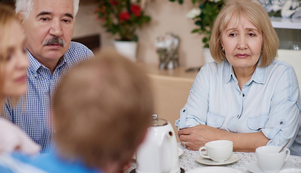 Group of four adult siblings sitting at a table having a serious conversation