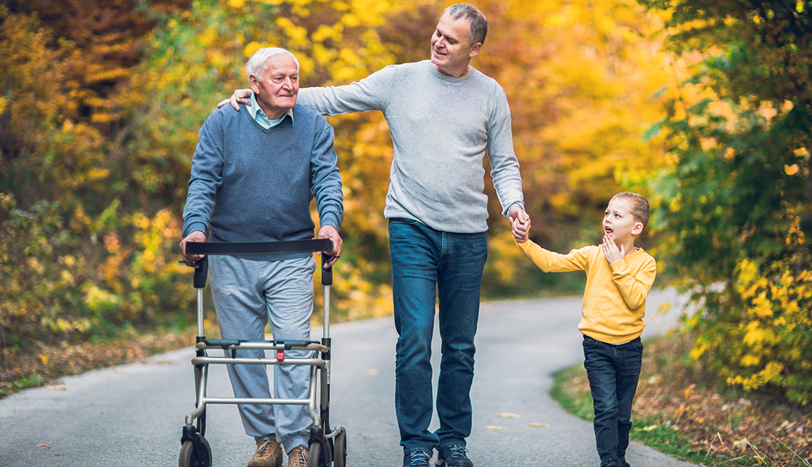 Man using a walker walks through a park with his adult son and young grandson