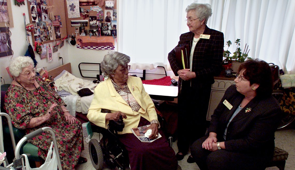 Two female nursing home residents in their room speak with two long term care ombudsman
