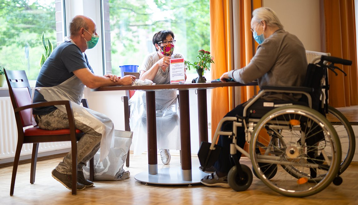 a couple and a man in a wheelchair sitting around a table in a nursing home wearing personal protective gear