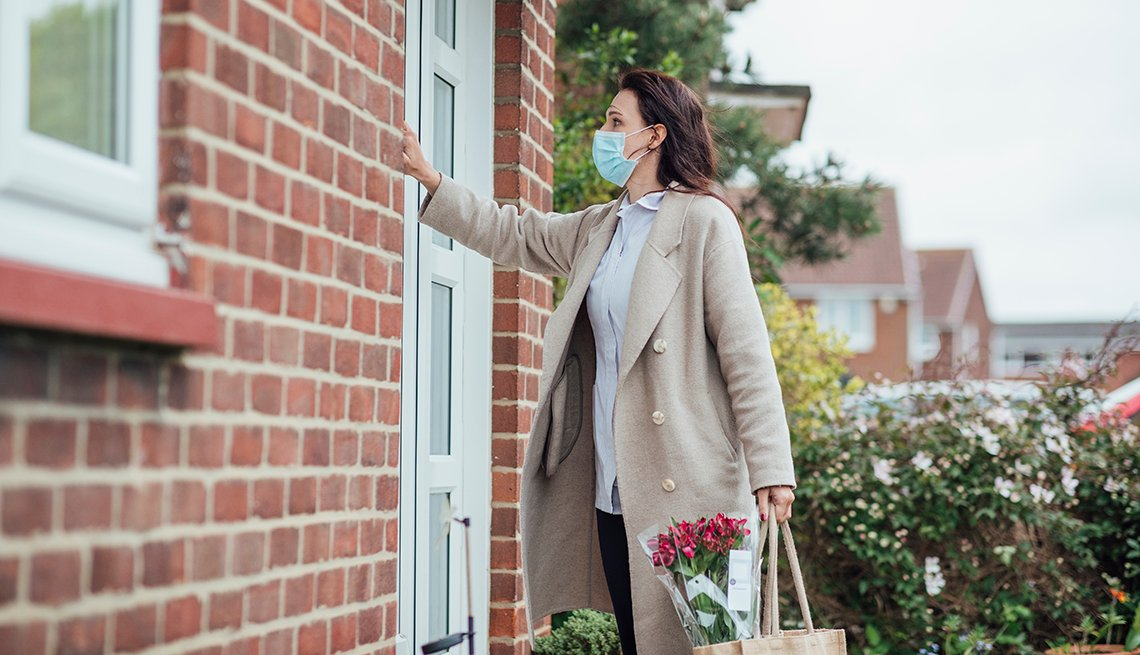 A woman wearing a face mask knocking on the front door of a home holding a bag and flowers