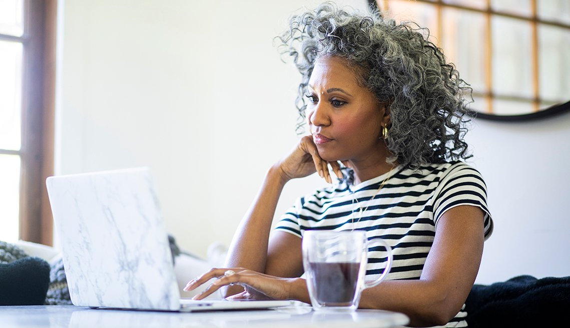Una mujer en su casa usa una computadora portátil