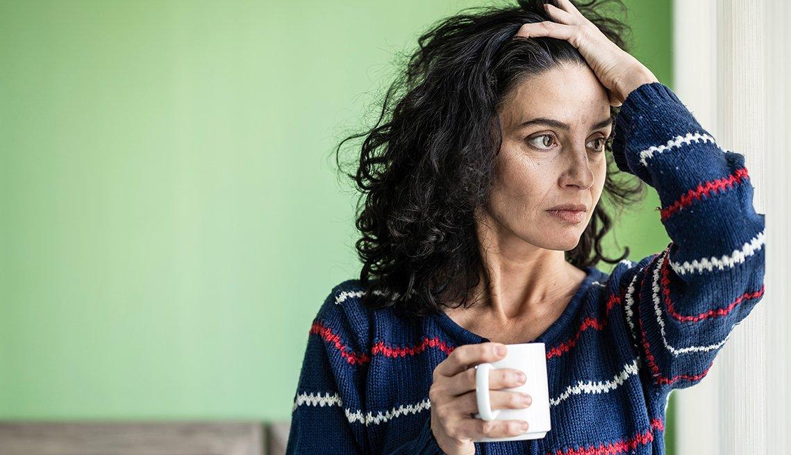 Una mujer con una taza en la mano y luce preocupada