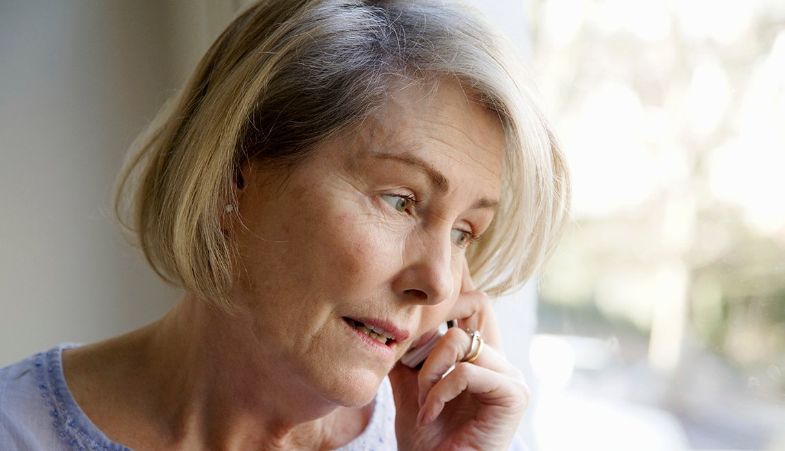 A worried looking woman on the telephone with an assisted living facility