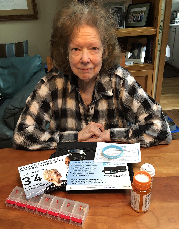 Andrée Jannette sentada en una mesa con un kit de atención consciente que incluye medicamentos y un frasco de pastillas