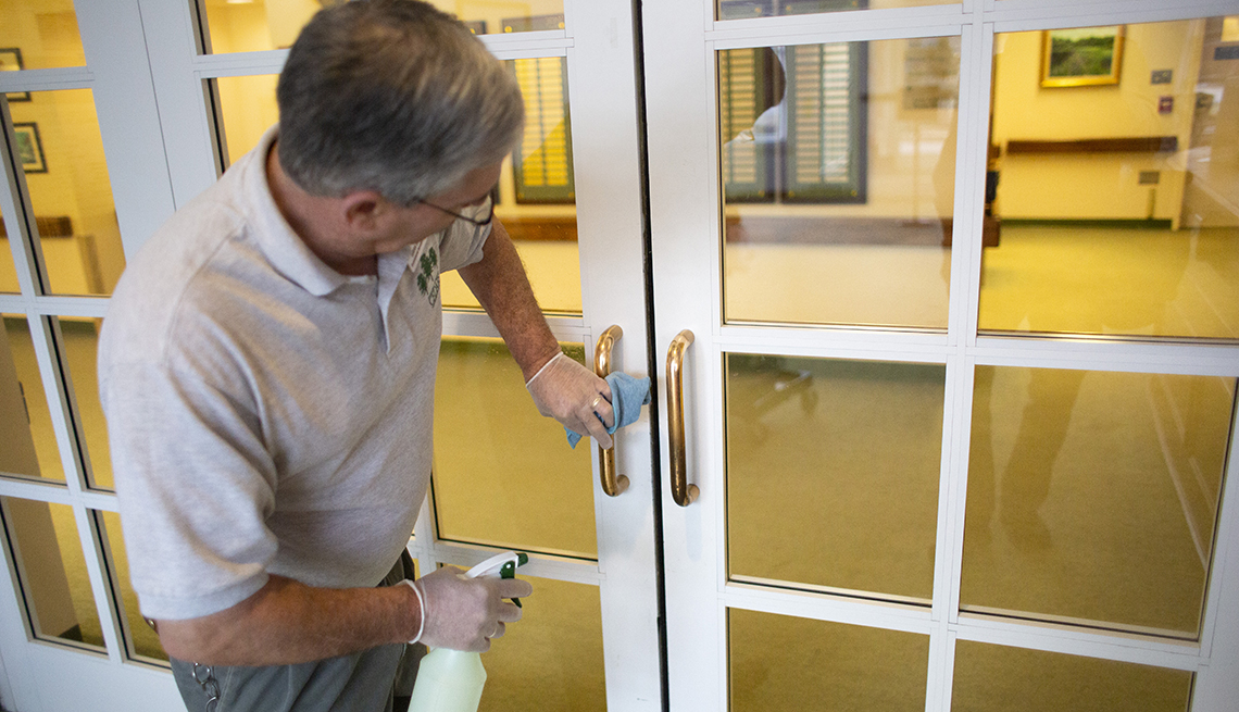 Man wearing gloves using disinfecting spray to clean a door handle at a nursing home