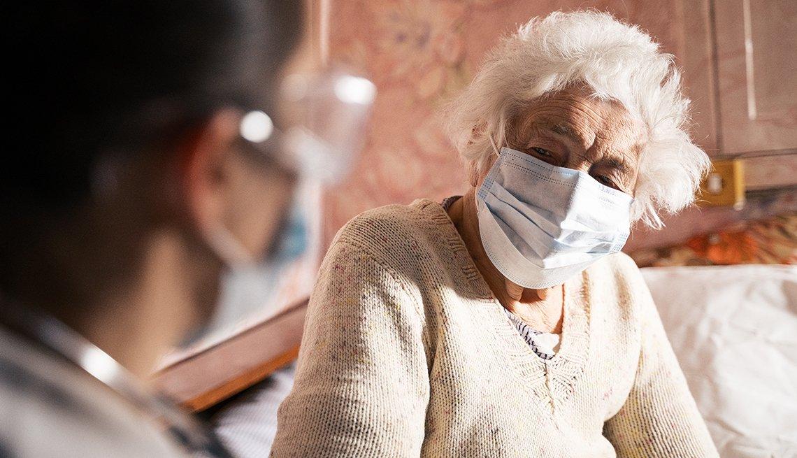 Doctora con EPP se sienta frente a un paciente con una mascarilla
