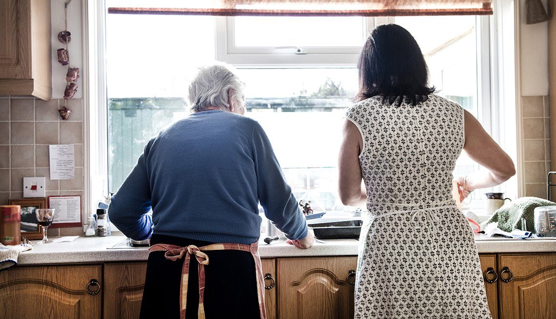 Rear view of a woman and her mother washing dishes together