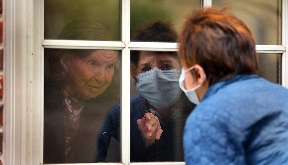 A woman is talking to another woman through a window