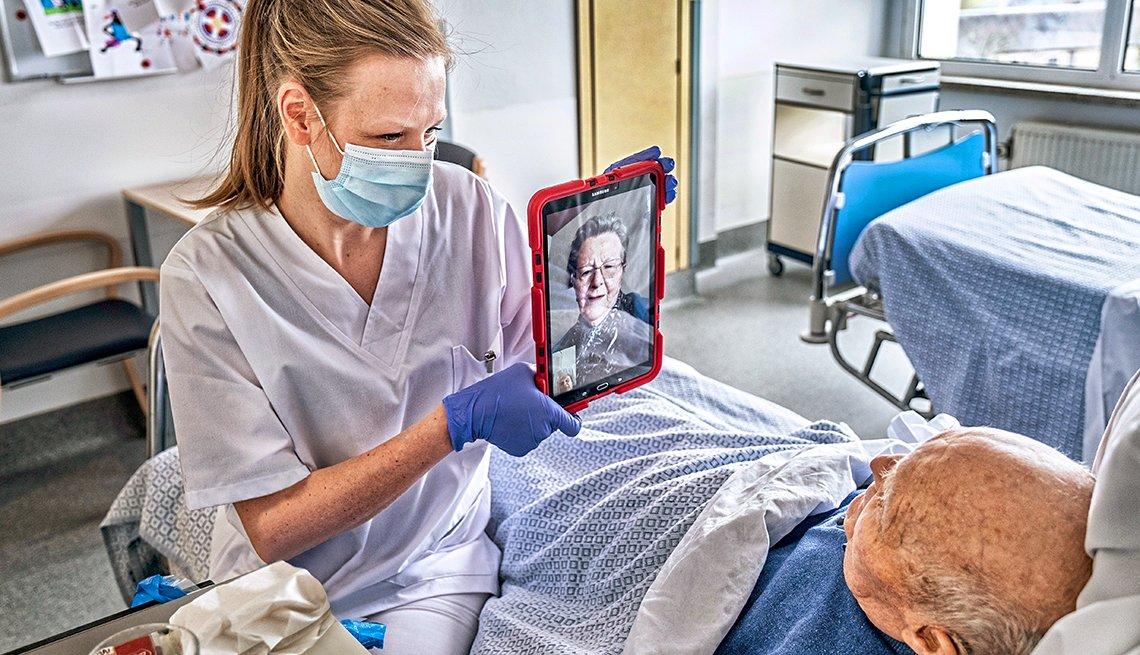 Una enfermera con una mascarilla sostiene una tableta para que un paciente se comunique con su familia