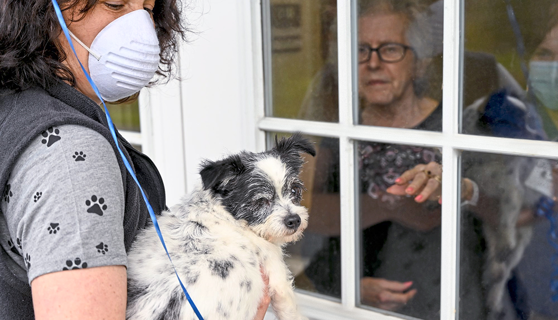Woman wearing a mask holding a small dog visiting a woman through a nursing home window