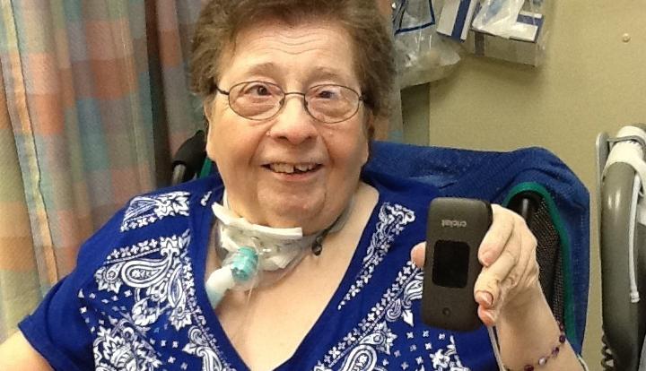 Ronni Ehrhart en la habitación de su hogar de ancianos sosteniendo su nuevo teléfono inteligente