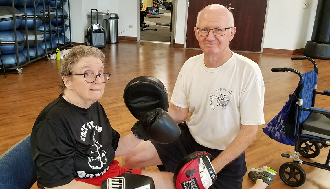Tom Manak and his wife Ro wearing boxing gloves at a fitness gym