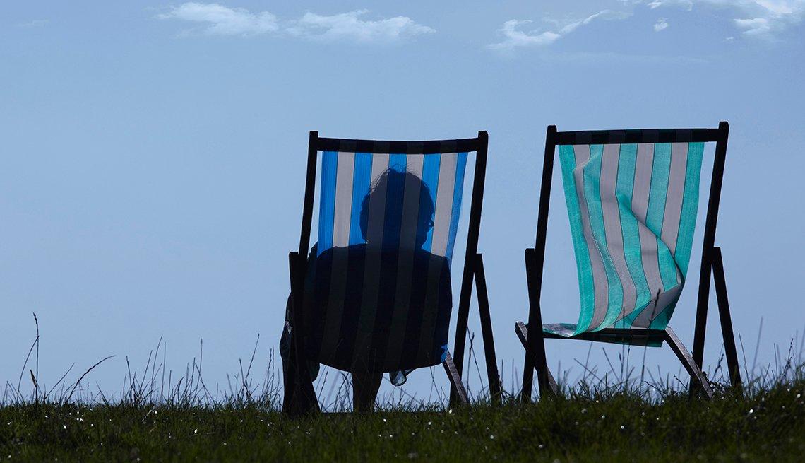 Silueta de una persona sentada en una silla de jardín