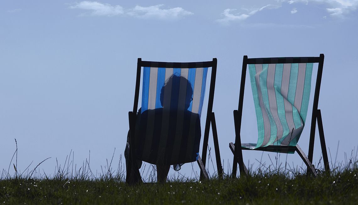 The silhouette of a woman sitting in a lawn chair next to a second empty lawn chair