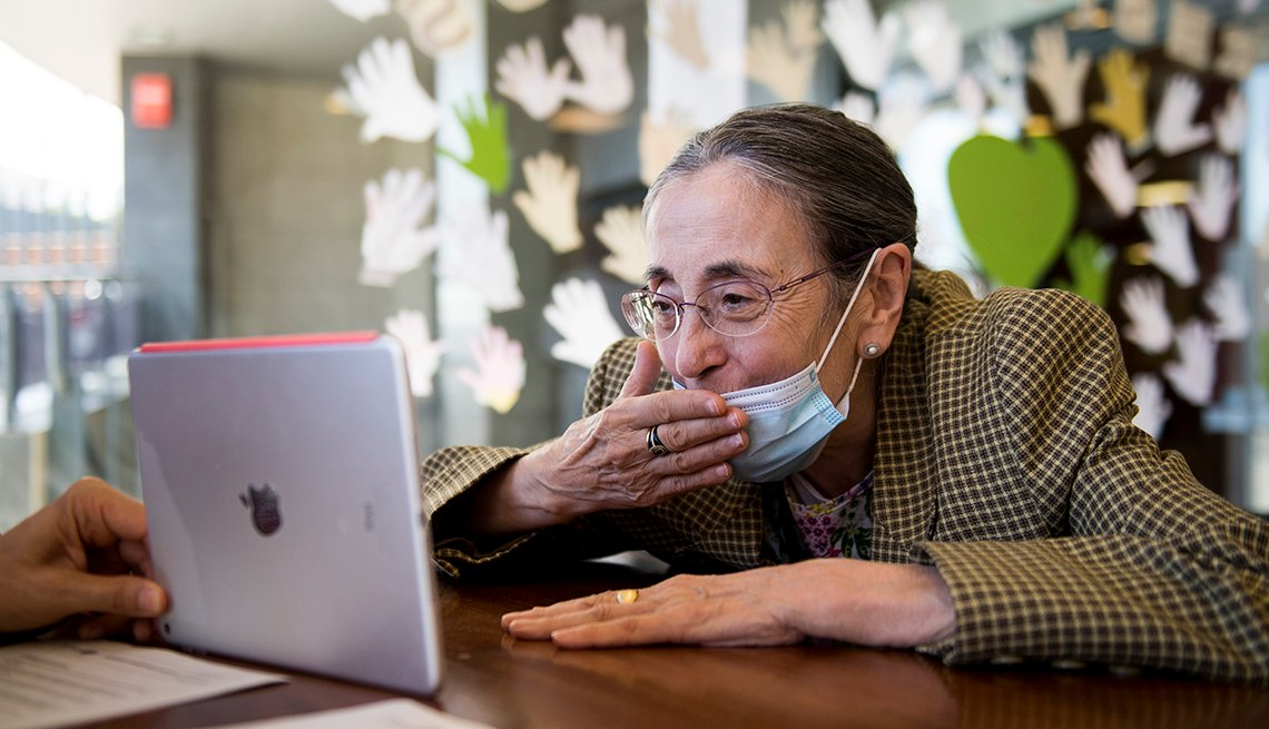 woman in a nursing home wearing a mask and blowing a kiss into a tablet that is being held by a care worker