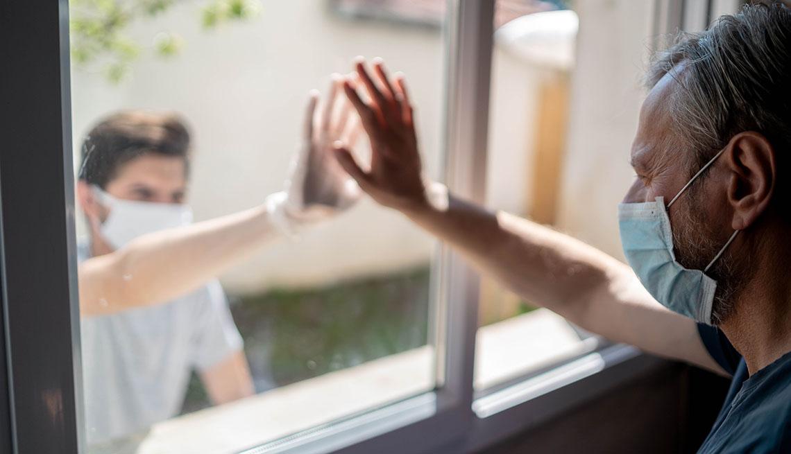 Un abuelo tocando la ventana interior y su nieto tocando la ventana desde el exterior. Ambos con mascarillas.