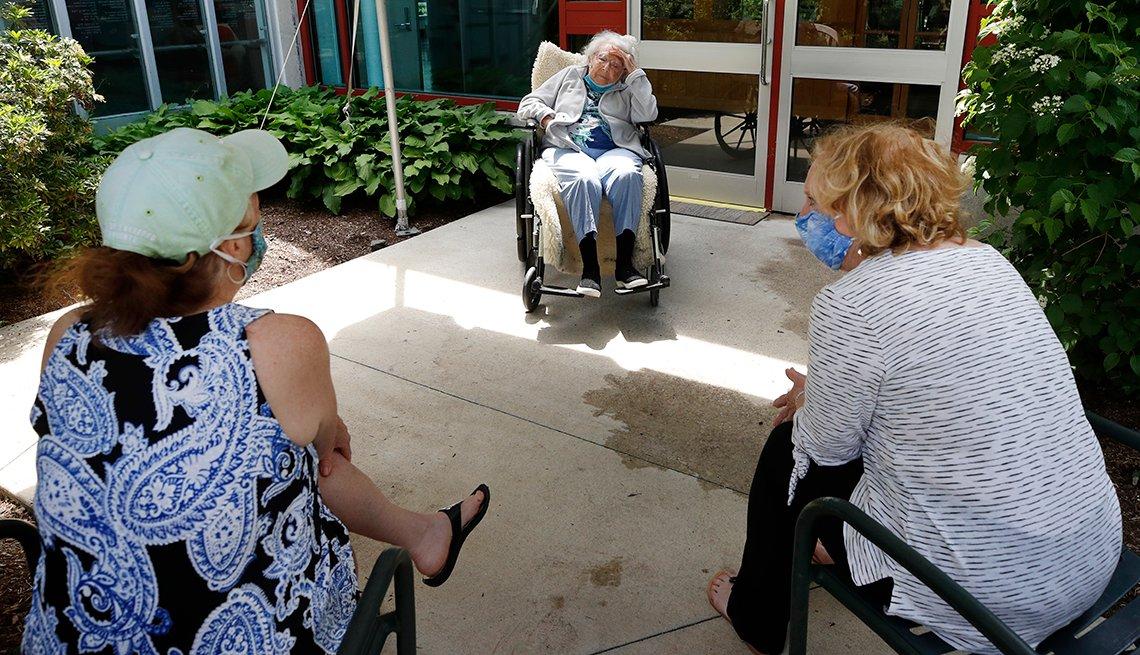 Dos mujeres con mascarillas visitan a su madre fuera de un hogar de ancianos