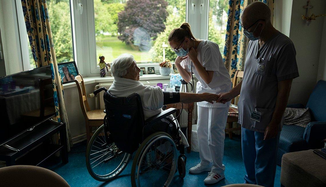Dos trabajadores con mascarillas visitan a un paciente en una silla de ruedas