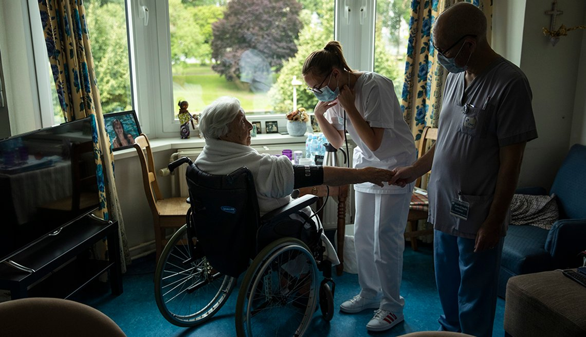 A woman in a wheelchair sits in her nursing home room being attended two by two nursing home staff members wearing face masks