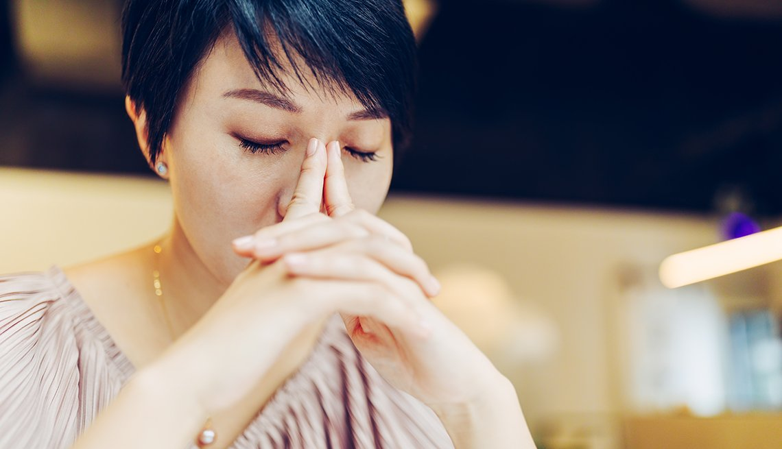 a stressed looking woman with her eyes closed and hands folded near her face