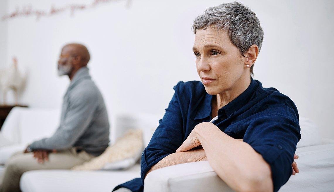 Una mujer que parece triste con su pareja en el sofá. Su pareja esta en la distancia mirando hacia adelante.