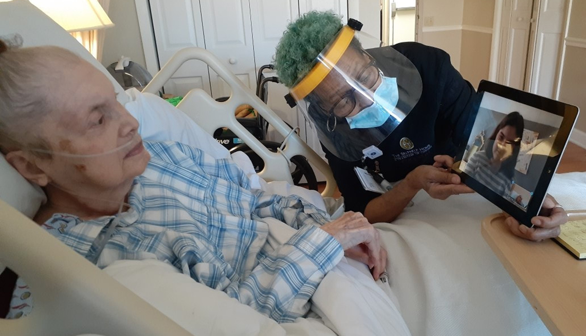 Un asistente de un hogar de ancianos que usa una mascarilla sostiene una tableta para que una mujer la vea en su cama