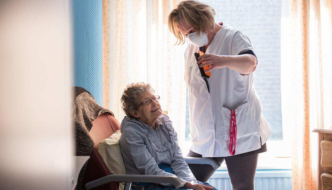 Un asistente de un hogar de ancianos sostiene un teléfono para ayudar a un residente de un hogar de ancianos con una visita virtual