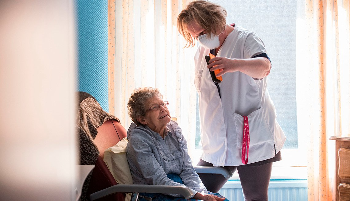 A nursing home aide holds a phone to assist a nursing home resident with a virtual visit